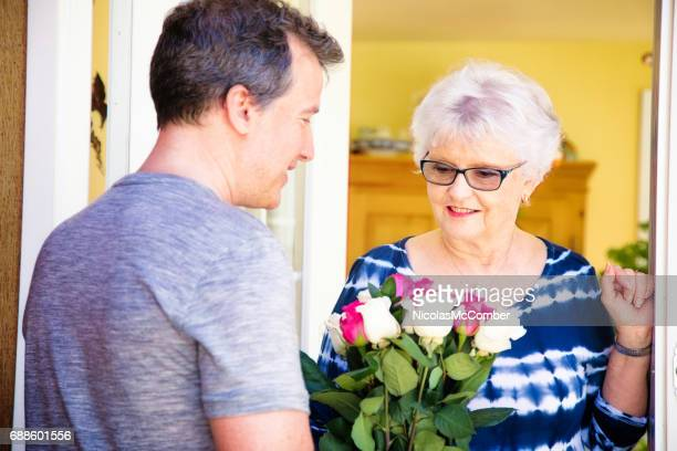 Senior woman happy to receive roses from mature son