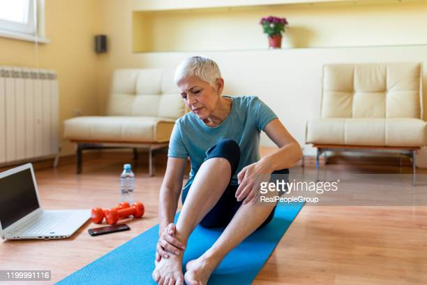 senior woman has ankle injury - injured stock pictures, royalty-free photos & images