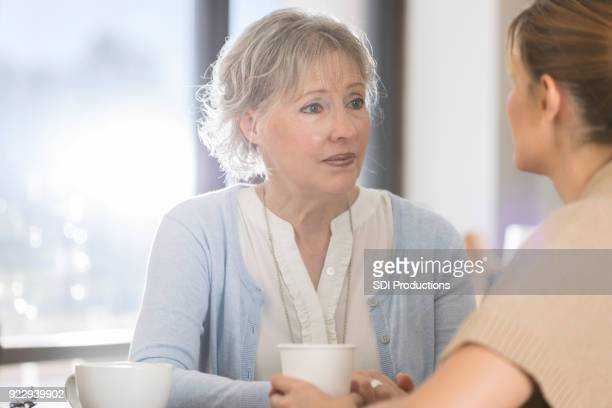 senior woman has serious conversation with daughter - vulnerability stock pictures, royalty-free photos & images