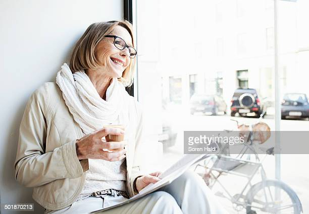 Senior woman having a coffee in cafe window seat