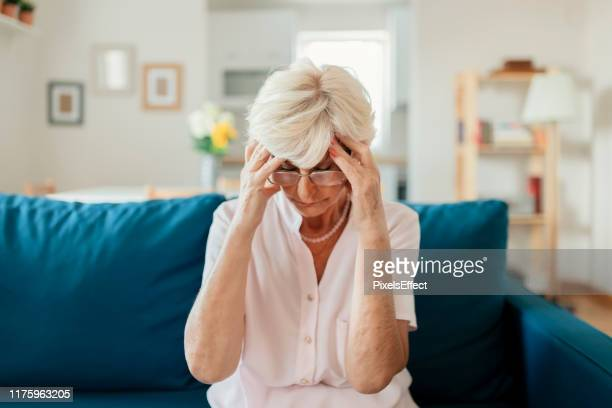 senior woman having a headache - position stock pictures, royalty-free photos & images