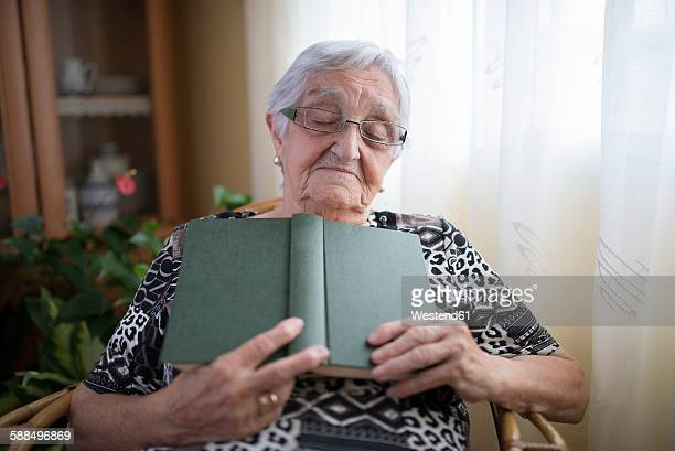 Senior woman having a nap with book in her hands at home