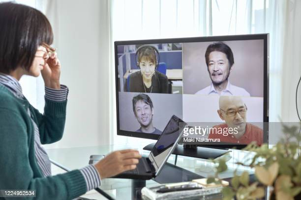 senior woman having a video conference at home. - テレビ会議 ストックフォトと画像
