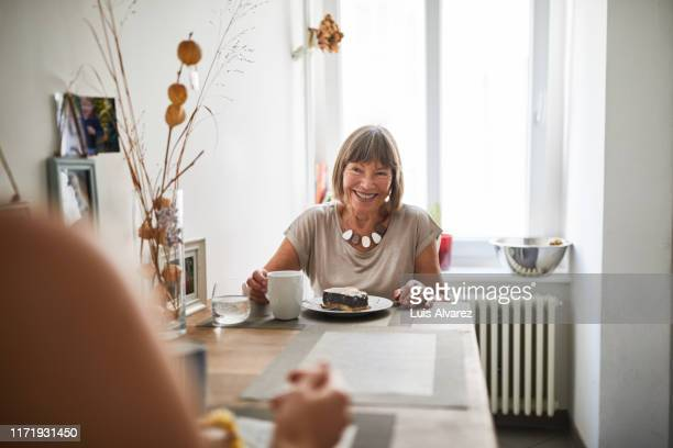 senior woman having breakfast with daughter in kitchen - senior women stock pictures, royalty-free photos & images