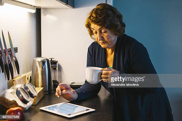 Senior woman having coffee while using tablet in her kitchen
