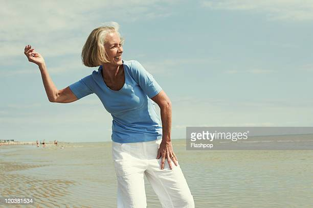 senior woman having fun at the beach - throwing stock pictures, royalty-free photos & images