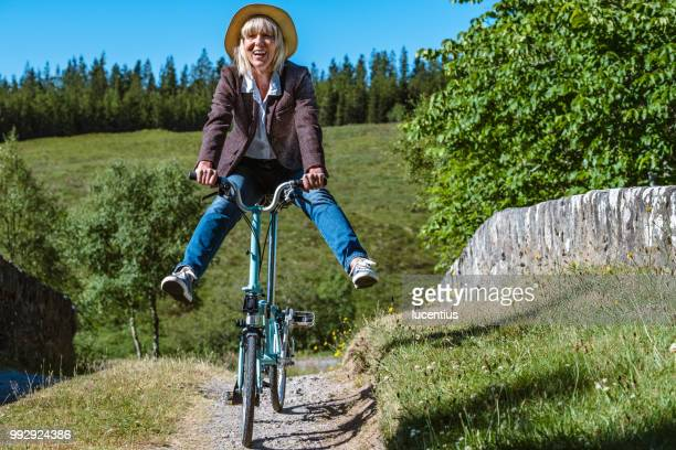 senior woman having fun on folding bike - foldable stock pictures, royalty-free photos & images