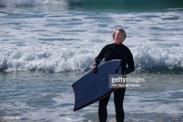 senior woman having fun with bodyboarding on the beach - finn bjurvoll stock pictures, royalty-free photos & images
