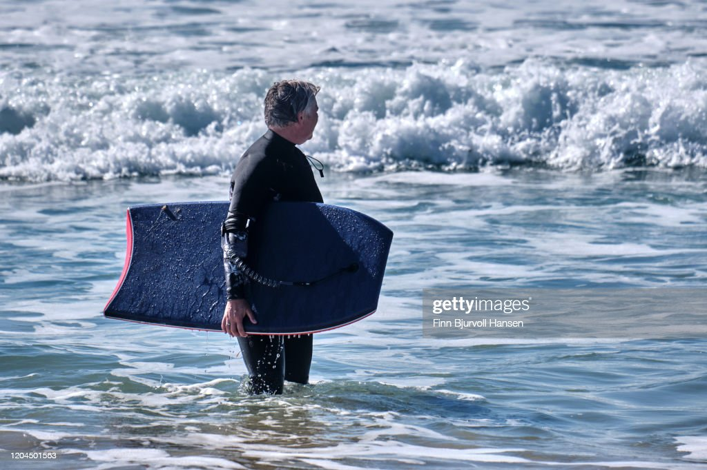 Senior woman having fun with bodyboarding on the beach : Stock Photo