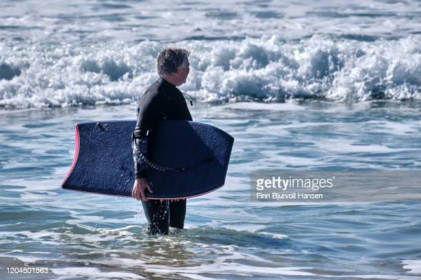 senior woman having fun with bodyboarding on the beach - finn bjurvoll ストックフォトと画像