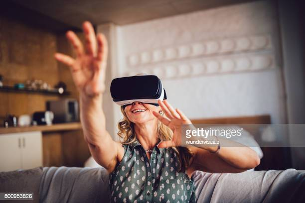 Senior woman having fun with virtual reality headset