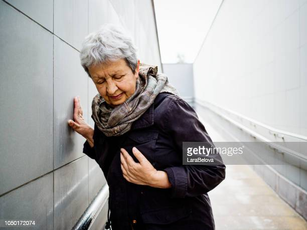 senior woman having heart attack - heart attack stock pictures, royalty-free photos & images