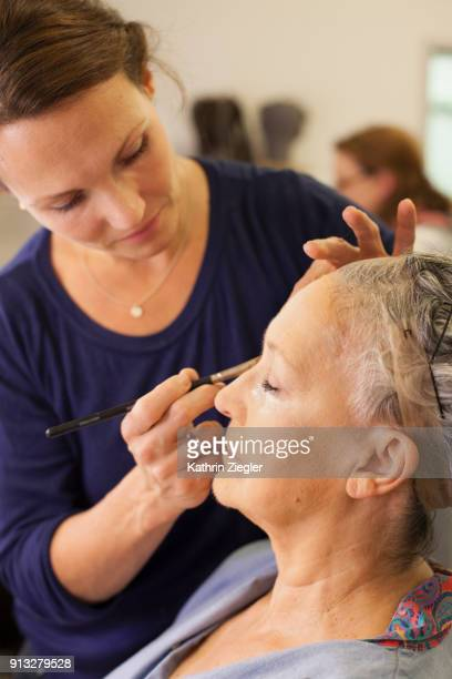 Senior woman having her makeup applied by makeup artist before stage performance