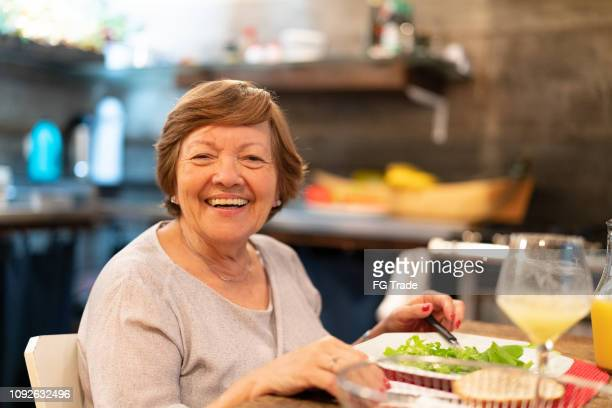 senior woman having meal at home - senior lunch stock photos and pictures