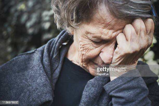 senior woman, head in hands, looks desperately tired and unhappy - vulnerability stock pictures, royalty-free photos & images