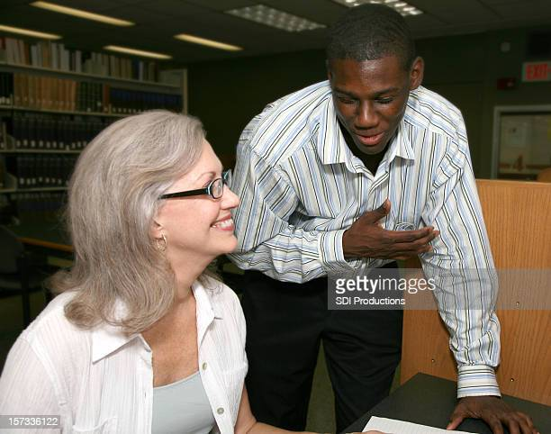 senior woman helping a male student in the library - teacher bending over stock photos and pictures