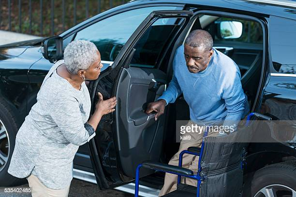 Senior woman helping disabled husband out of car