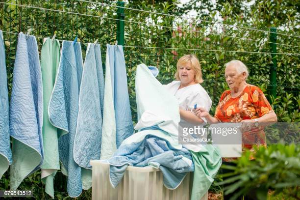 senior woman helping hanging laundry on the washing line at the nursing home - residential care stock photos and pictures