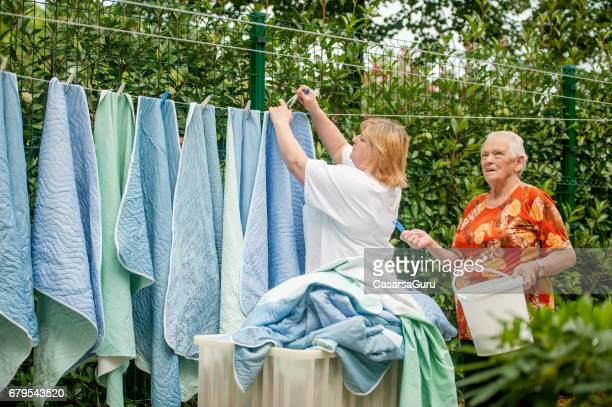 Senior Woman Helping Hanging Laundry On The Washing Line At The Nursing Home