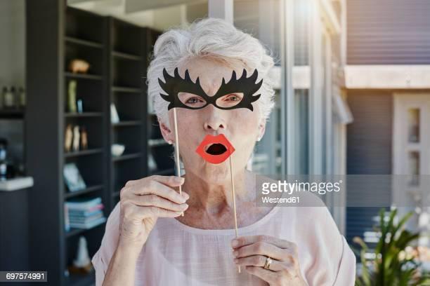 senior woman hiding behind paper masks - nur erwachsene stock-fotos und bilder