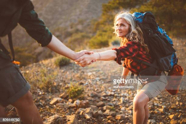 Senior woman hiker holding man's hand to climb on mountain