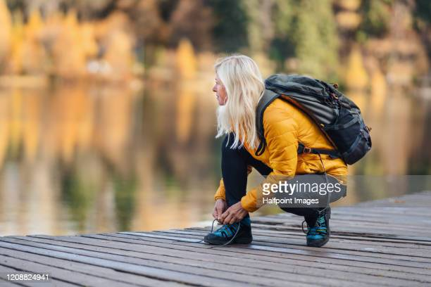 a senior woman hiker in autumn nature, tying shoelaces by lake. - tying shoelace stock pictures, royalty-free photos & images