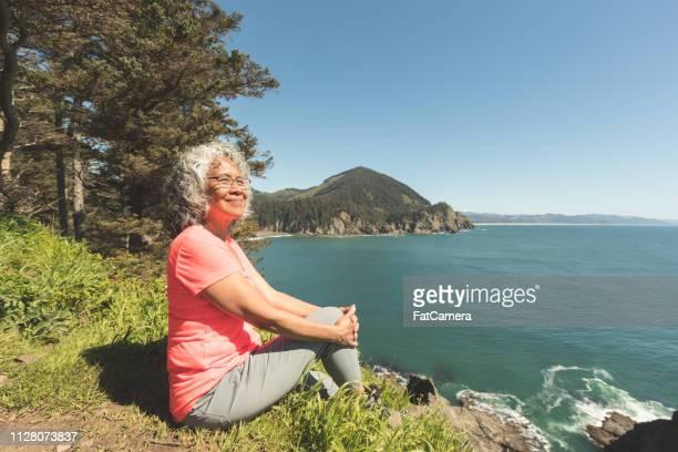 senior woman hiking on the oregon coast - oregon coast stock pictures, royalty-free photos & images