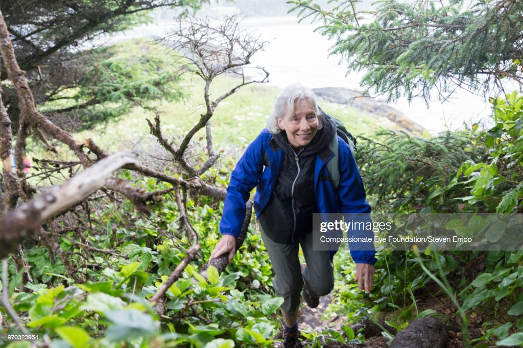 Senior woman hiking up forest trail near ocean : Stock Photo