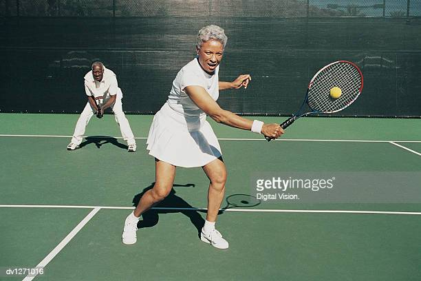 senior woman hitting a tennis ball on a tennis court and a senior man standing behind - tennis stock pictures, royalty-free photos & images