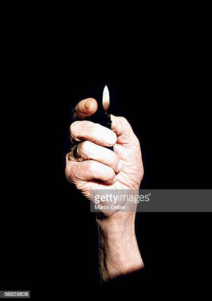 senior woman holding a lighter - cigarette lighter stock pictures, royalty-free photos & images