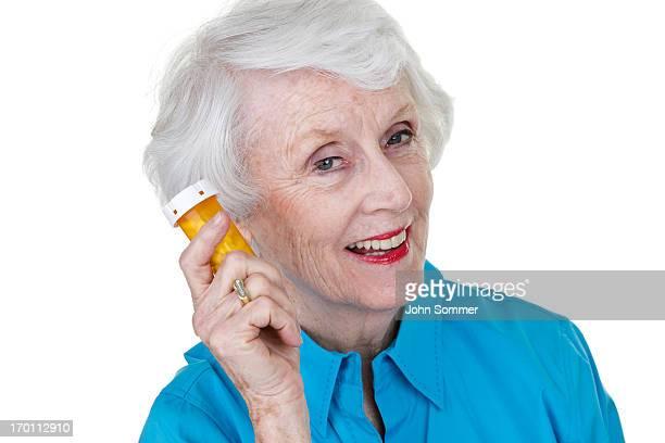 senior woman holding a medicine container - medicijnen innemen stockfoto's en -beelden