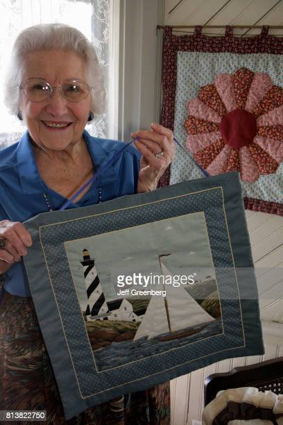 A senior woman holding a quilt at The Seven Gables House visitor information center and museum