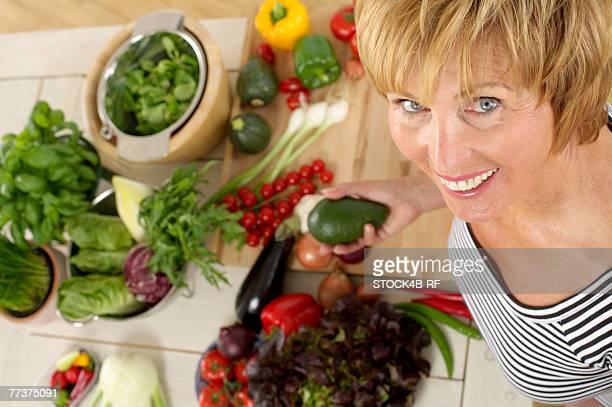 Senior woman holding an avocado smiling at camera