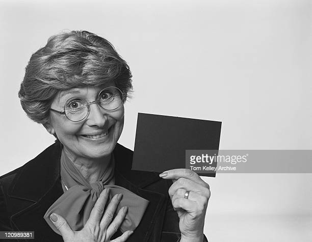 senior woman holding blank placard against white background, close-up - 1980 stock pictures, royalty-free photos & images