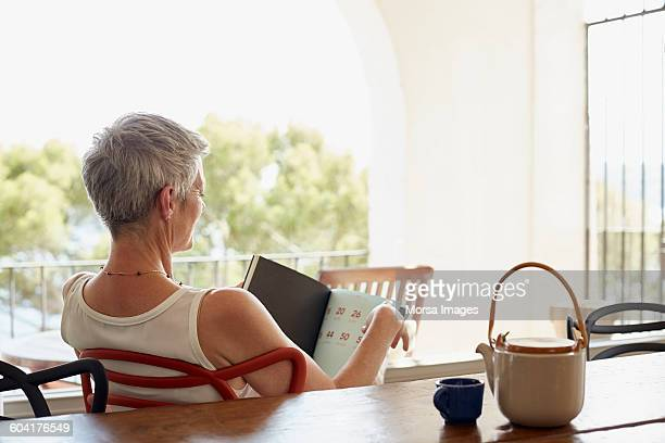 Senior woman holding book while siting on chair