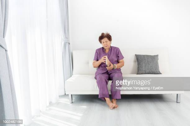 Senior Woman Holding Book While Sitting On Sofa At Home