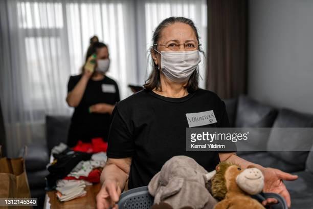 コーヴィッド-19の間に慈善のための寄付の箱を保持するシニア女性 - ホームレスシェルター ストックフォトと画像
