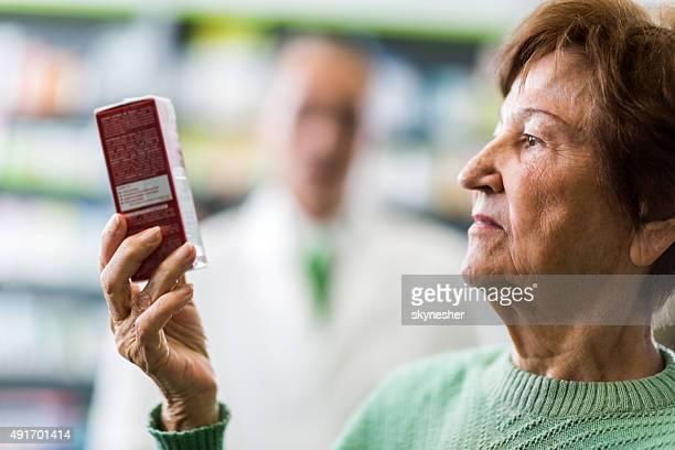 Senior Frau hält Karton der Medizin in Apotheke.