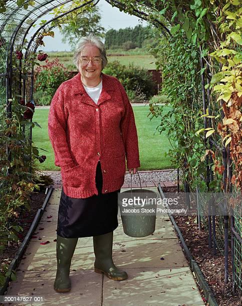 Senior woman holding bucket, standing under garden arch, portrait