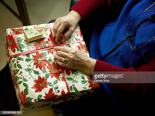 Senior woman holding Christmas gift, mid section, elevated view