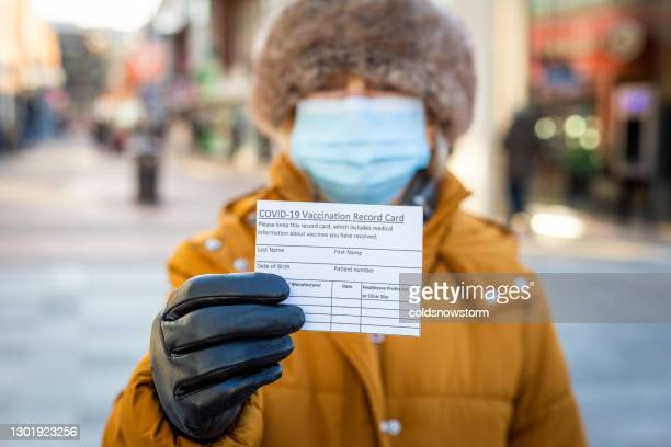 senior woman holding covid-19 vaccination record card on city street - winter stock pictures, royalty-free photos & images