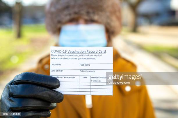 senior woman holding covid-19 vaccination record card on city street - certificate stock pictures, royalty-free photos & images