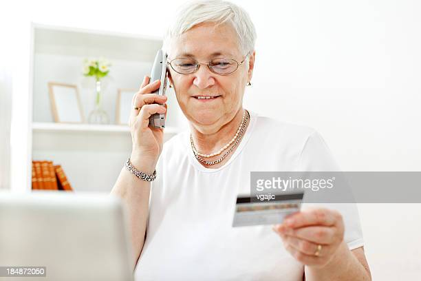 Femme âgée tenant TeleShopping une carte de crédit en ligne