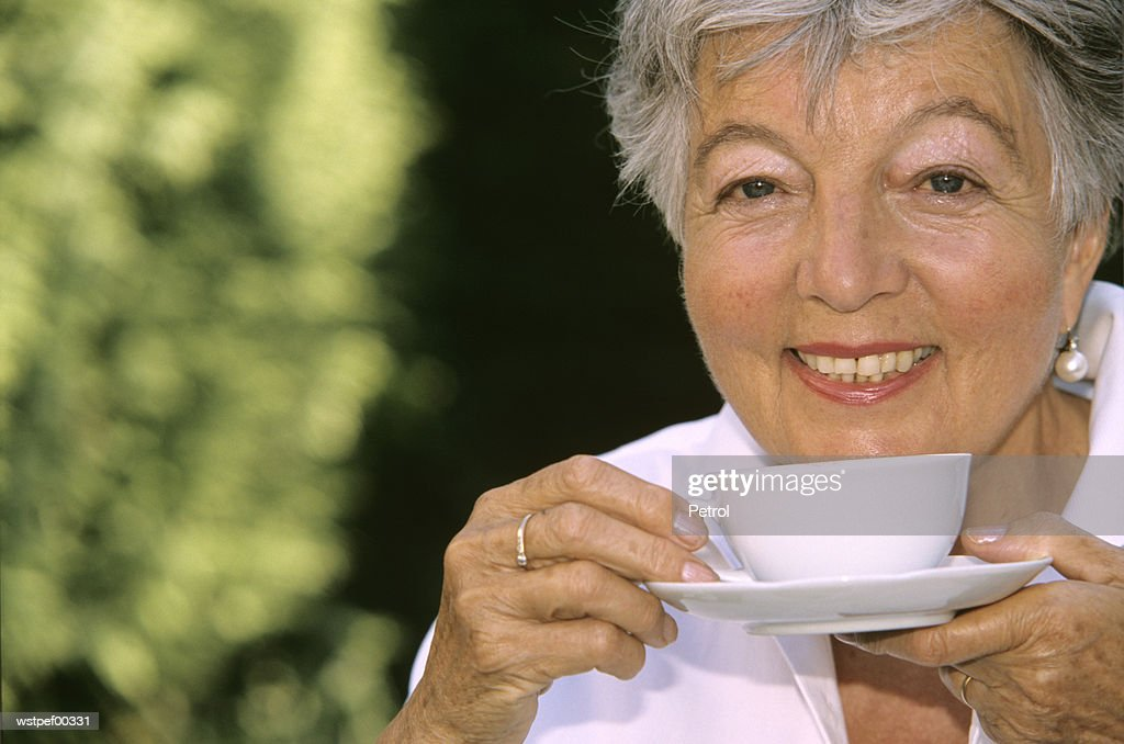 Senior woman holding cup of coffee, close up : Stock Photo