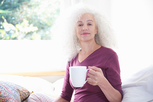 senior woman holding cup of coffee in house - gettyimageskorea