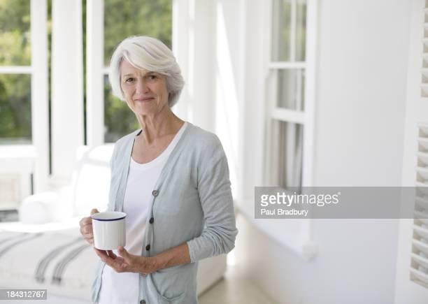 Senior Frau holding Tasse Kaffee in sun room