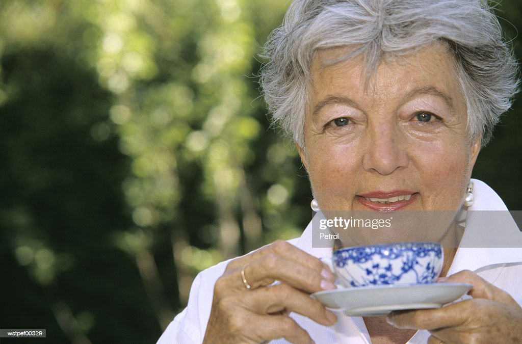 Senior woman holding cup of tea, close up : Foto de stock