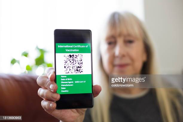 senior woman holding digital covid-19 vaccine passport on her smart phone - certificate stock pictures, royalty-free photos & images