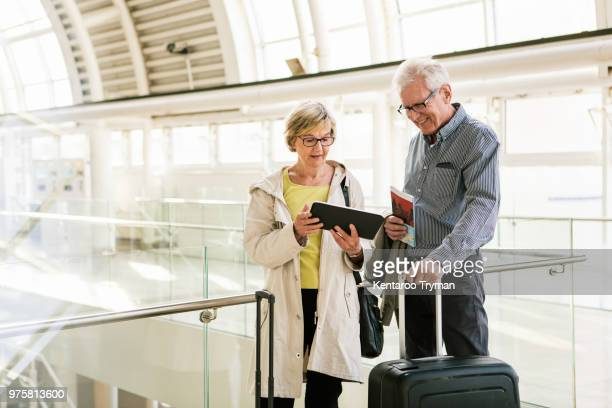 Senior woman holding digital tablet by man standing with luggage atstation
