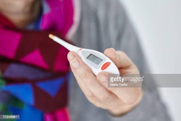senior woman holding digital thermometer, close-up - digital thermometer ストックフォトと画像